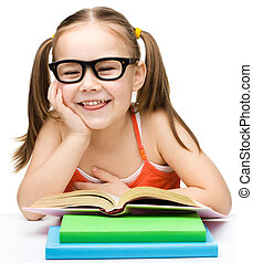 Cute cheerful little girl reading book while wearing glasses...