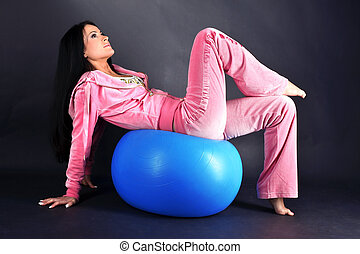 relaxing woman in sport outfit with blue ball