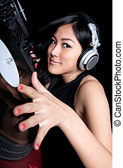 Female DJ mixing on turntables - A female DJ mixing on a...