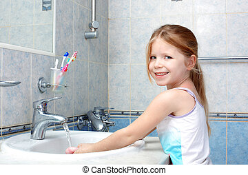Little girl washing with soap in bathroom