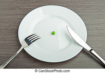 diet concept one pea on an empty white plate with knife and...