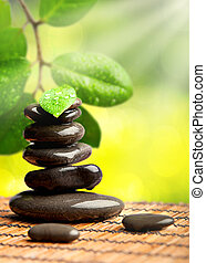 spa green background. stones with water drops