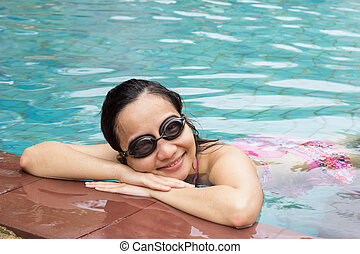 Young woman with swimming glass smiling in pool