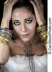 Woman lying and sensual with bracelets of gold and silver, looking