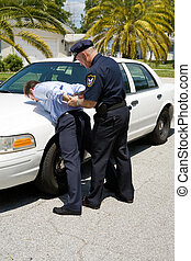 Arresting Drunk Driver - Police officer placing a drunk...