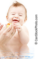laughing baby boy in water playing with rubber duck -...