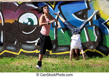modern dancers in sity against graffiti wall