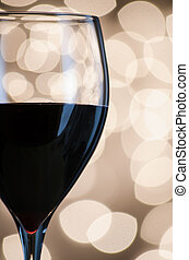 Red wine against blurred lights - Closeup of a glass of red...
