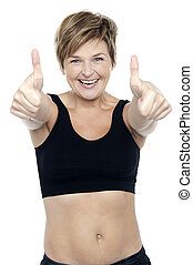 Excited attractive fit lady showing double thumbs up -...