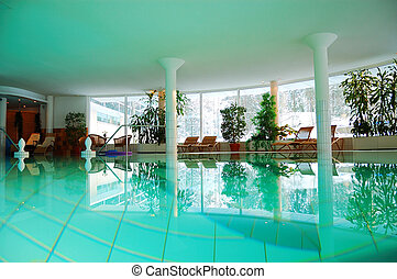 Interior of a spa hotel with turquoise water in the swimming pool