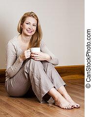 casual woman - pretty blond woman wearing beige top relaxing...