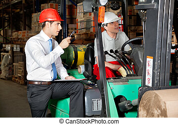 Supervisor With Clipboard Instructing Forklift Driver - Male...