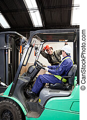 Forklift Driver Communicating With Colleague