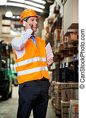 Supervisor Using Cell Phone At Warehouse - Portrait of young...