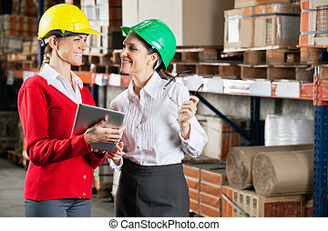 Female Supervisors Discussing Work At Warehouse