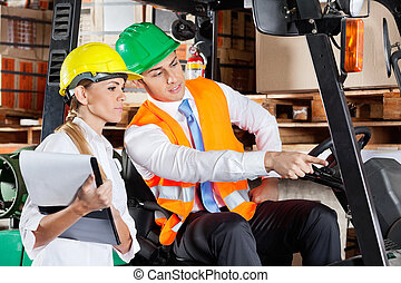 Male Supervisor Showing Something To Colleague At Warehouse