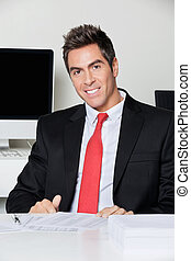 Happy Businessman Sitting At Desk - Portrait of happy young...