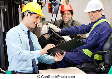 Male Supervisor Communicating With Forklift Driver And Foreman