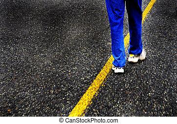 Walking Down Road - Person wearing blue jeans walking down...