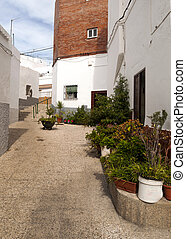 Sloping cobbled street with pots in the street, is located...