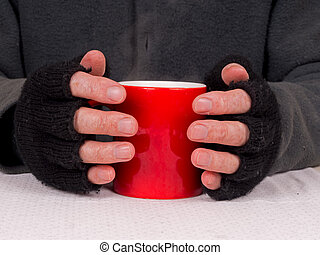 Mug of steamingsoup poverty concept - Man in fingerless...