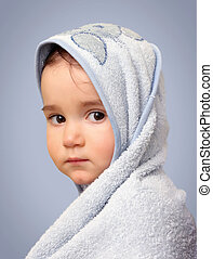 Angel look baby boy portrait with towel on blue background