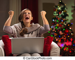 Happy woman with laptop rejoicing success in front of...