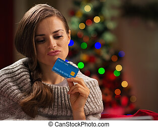 Thoughtful woman in front of Christmas tree holding credit...