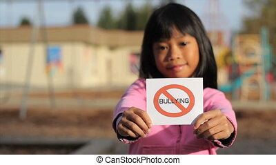 Girl Holding A NO BULLYING Sign - A cute Asian girl holds up...