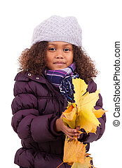 Portrait of a little african asian girl wearing winter clothes playing with leaf trees, isolated on white background