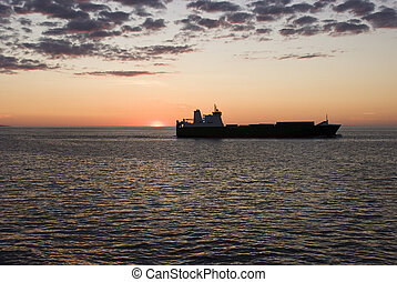 Cargo container ship in sunset
