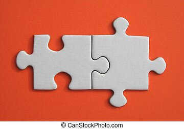 White jigsaw puzzle pieces on orange paper background