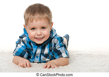 Cheerful little boy on the white carpet