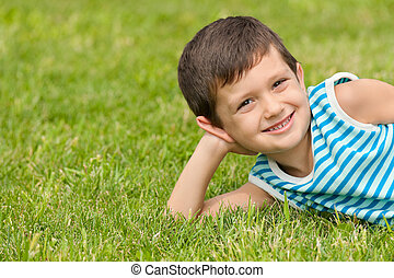 Joyful little boy on the grass - Joyful little boy lying on...