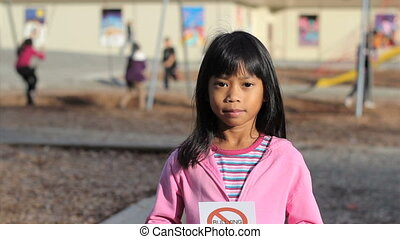 No Bullying Message On Playground - A cute Asian girl holds...