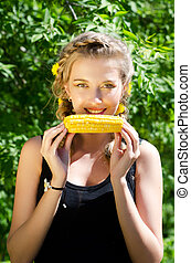 woman eating corn-cob - Close-up outdoor portrait of young...