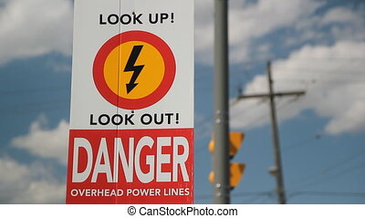 Overhead power lines - A sign warns of the danger of...