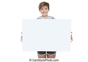Charming young woman holding white ad board - Charming...