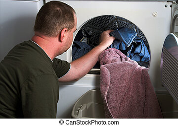 Doing Laundry - A man taking laundry out of a clothes dryer