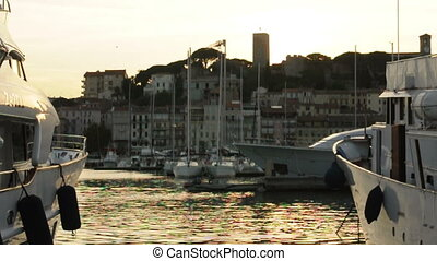 Yachts moored in Cannes at sunset.