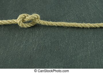 a rope with a knot in it lying on a slate stone