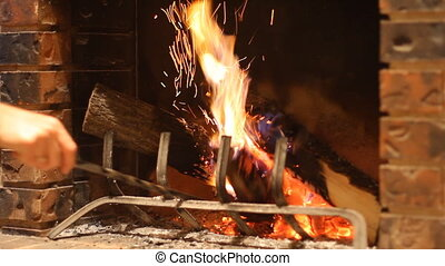 Fireplace - Man burns wood in a stone fireplace at home in...