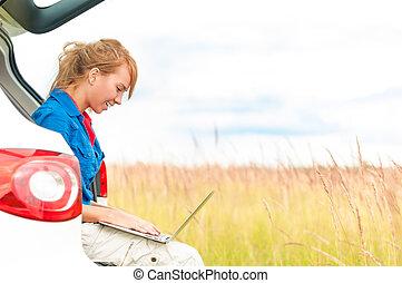Woman in meadow near car working on laptop.
