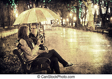Couple sititng at bench in night lights. Photo in vintage multicolor style.