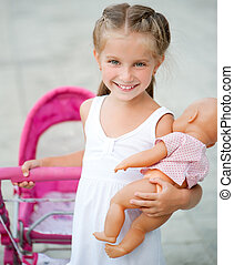 little girl with toy carriage - Cute little girl with her...