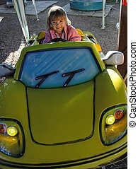 Funny car driving - Little girl driving a carrousel car in a...