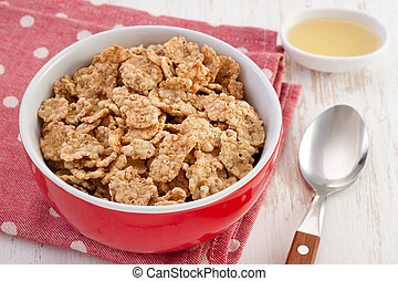 cereals in the bowl with honey and spoon