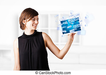 Young woman looking at modern tablet with social icons -...