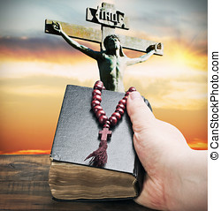 hand holds the bible on the background of the Crucifixion of...