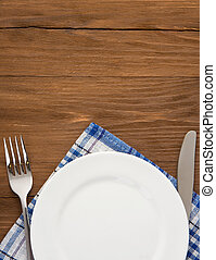 white plate, knife and fork on wood - white plate, knife and...